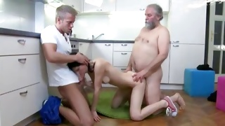 Grey bearded man is taking the clothes off a little beauty