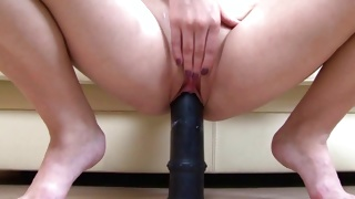Bizarre lassie is sexually riding on the huge big dildo